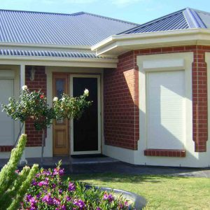 Cream roller shutters on brick home