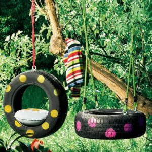 Painted tyre swings hanging from tree